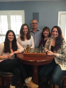 Caitlyn Picard | Picard (far right) sits at a game of chess with her family, including her father (center). This photo was recently used for one of his campaigns.